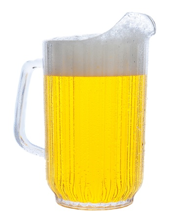 Pitcher of beer in vertical format over white.