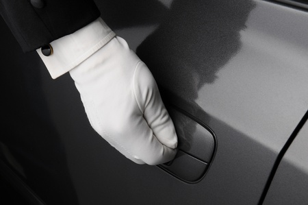 guantes: Primer plano de una mano doormans en el pestillo de una puerta de coche. Foto de archivo