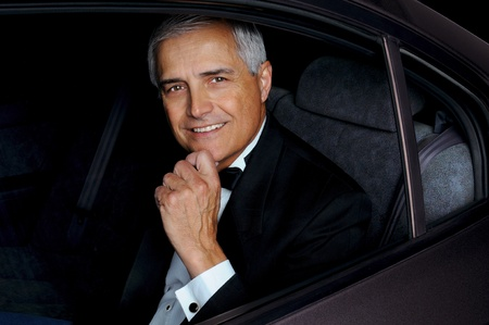 Closeup of a middle aged man wearing a tuxedo and seated in the back seat of a car.