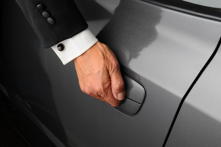 cuff link: Closeup of a mans hand on the latch of a car door. Person is wearing a tuxedo. Stock Photo