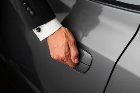 courtoisie: Gros plan d'une main mans sur le loquet de la porti�re d'une voiture. Personne est v�tu d'un smoking. Banque d'images