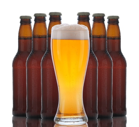 A glass of foamy beer with six brown bottles grouped behind over a white background with reflections Stock Photo - 12853785