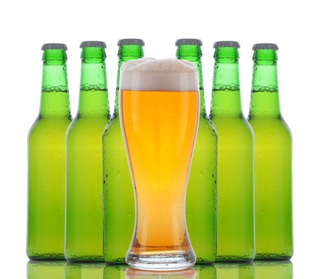A cold frosty glass of beer in front of a group of green bottles on a white background. Horizontal with reflection. Stock Photo - 12853801