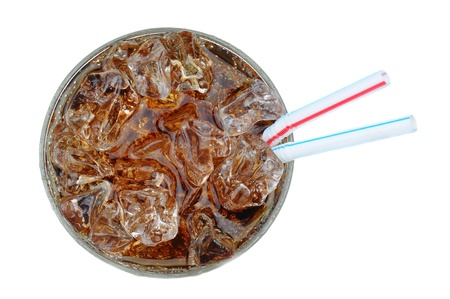 Top view of a glass full of ice and cola with two drinking straws over a white background. photo