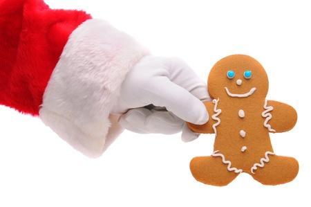 galleta de jengibre: Papá Noel mano que sostiene el hombre de pan de jengibre en un vackground blanco