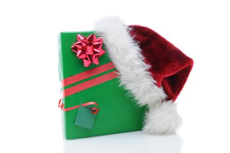 Santa Claus hat on the corner of a wrapped christmas present. Horizontal format over a white background. Stock Photo - 12853803