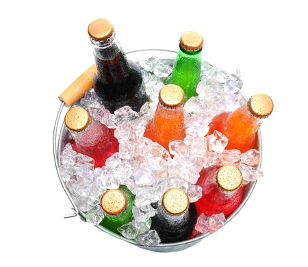 Top view of a bucket full of ice and soda bottles. Isolated over a white background. photo