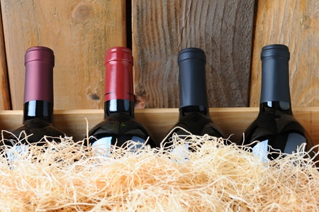 Closeup of four different wine bottles in a wooden crate with straw packing material. photo