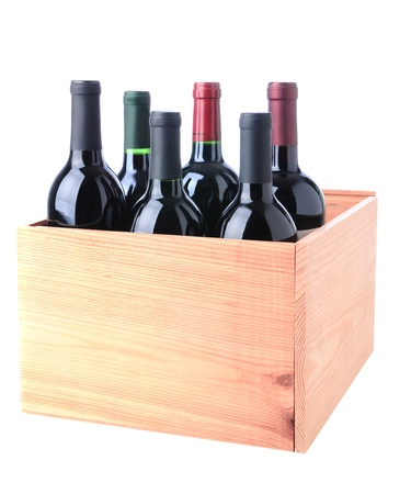 An assortment of Red Wine bottles standing in a wooden crate isolated on a white background. photo