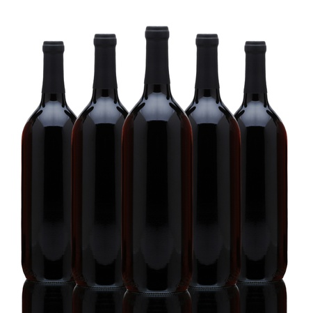 A arrangement of five red wine bottles over a white background. Horizontal format with reflection. photo