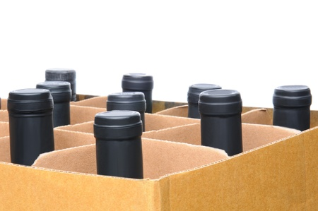 Closeup of wine bottles in a cardboard box  Horizontal format over a white background with shallow depth of field