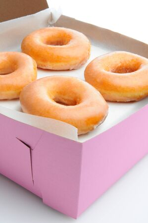 Closeup of four glazed donuts in a pink bakery box  Vertical format with a white background Stock Photo - 13041561