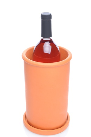 white zinfandel: A terra cotta wine chiller with a bottle of blush wine inside. Vertical over a white background with reflection.