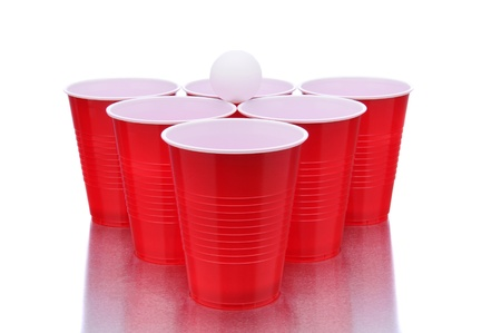 Red cups and a ping pong ball on a white surface with reflection. Beer Pong concept in horizontal format.
