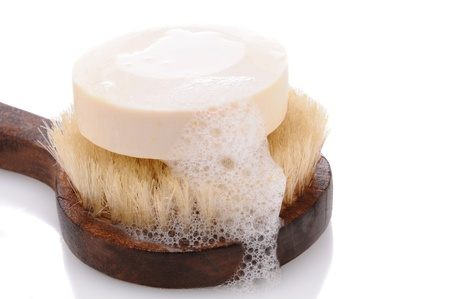 soap suds: A bar of soap with lather on a bath brush with a wooden handle. Horizontal format over a white background with reflection.