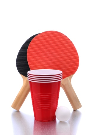 table tennis paddles and ball with cups for playing Beer Pong on a white background with reflection. photo
