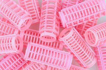 Plastic pink hair curlers in a random pattern that fills the frame.