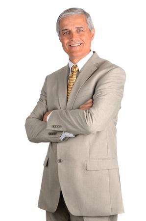 podnikatel: Portrét usmívající se podnikatel středního věku v světlo obleku s rukama založenýma na prsou. Tři čtvrtiny pohled na bílém pozadí.