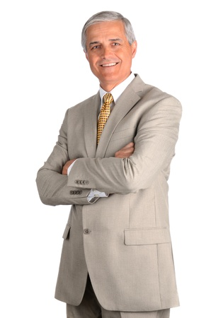 Portrait of a smiling middle aged businessman in a light suit with his arms folded. Three quarters view over a white background. Stock Photo