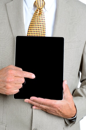 Closeup of a businessman in a suit pointing at the screen of a tablet computer. Man is unrecognizable, with tablet held in front of his torso. photo