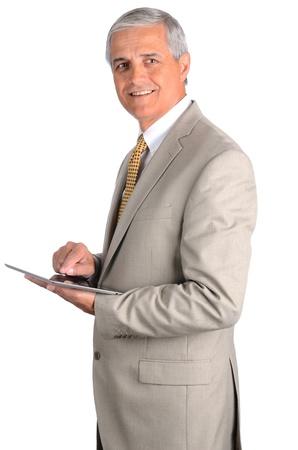 13387504 - Retrato de un sonriente hombre de negocios de mediana edad con  un traje claro con un equipo Tablet PC. Tres cuartas partes de vista sobre  un ... 0e64a849b66
