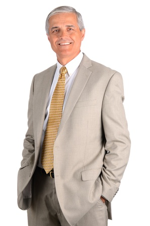 business men: Smiling middle aged businessman with his hands in his pockets. Three quarters  over a white background.