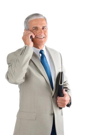 m�s viejo: Hombre de negocios de mediana edad hablando por su tel�fono celular y llevar un cuaderno. El hombre est� sonriendo y mirando a la c�mara sobre un fondo blanco.