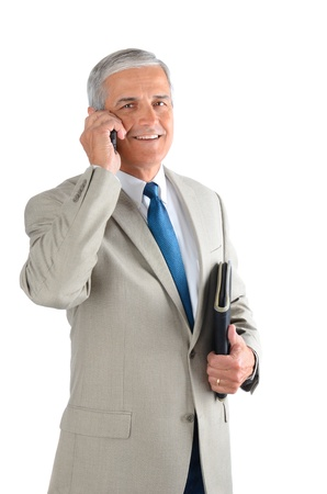 Middle aged businessman talking on his cell phone and carrying a binder. Man is smiling and looking at camera over a white background. photo