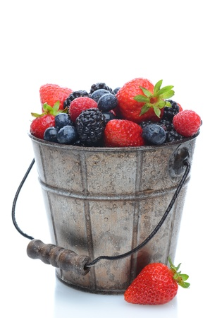 Assorted fresh picked berries in a pail with a wooden handle over a white background. Vertical format with reflection.