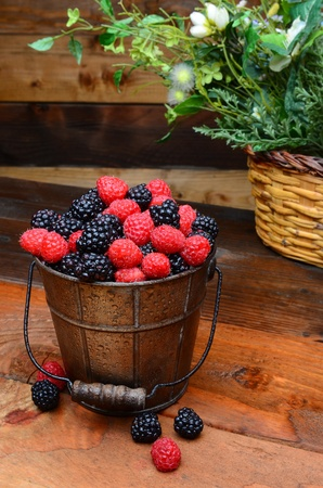 Fresh picked blackberries and raspberries in a galvanized pail on a rustic wooden table. Vertical format photo