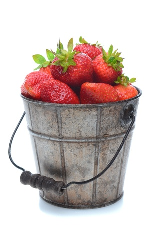 A pail full of freshly picked strawberries. Vertical format isolated on a white background with slight reflection. Stock Photo - 13467401