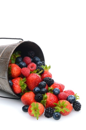 A pail laying on its side with assorted berries spilling out. Vertical format with copy space. photo