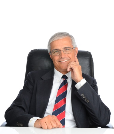 Portrait of a seated mature businessman with his hand next to his face. Man is smiling and wearing eyeglasses, over a white background. Stock Photo
