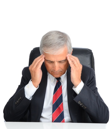 Mature businessman seated at his desk holding his temples to ease a migrane headache. Square format over a white background. photo