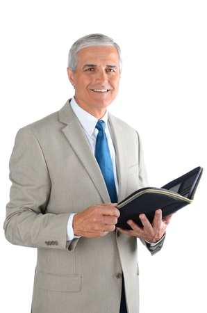Portrait of a middle aged businessman over a white background. Man is holding an open notebook in vertical format.