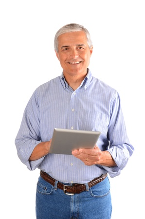 casually: A casually dressed businessman holding a tablet computer, and smiling at viewer. Vertical composition over a white background.