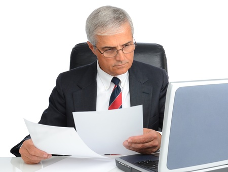Mature businessman at desk comapring note to laptop screen. Man is wearing eye glasses over a white background. Stock Photo - 13467485