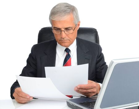 Mature businessman at desk reading papers. Man is wearing eye glasses and has a laptop computer. photo