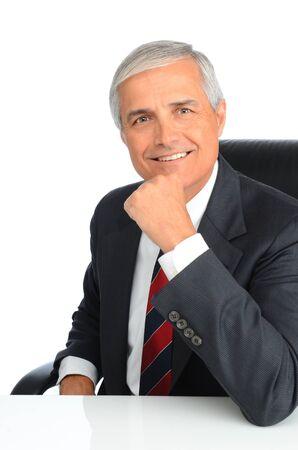 자신의 손으로 자신의 턱 함께 책상에 앉아 성공적인 성숙 사업가의 초상화입니다. 남자는 웃 고있다. 흰색 배경 위에 세로 형식입니다.