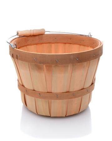 bushel: Empty bushel basket with a wood handle and stuffed with straw over a white background and slight reflection. Stock Photo