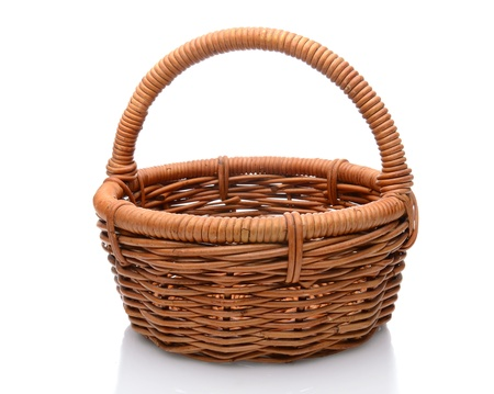interleaved: Round brown wicker basket with handle isolated on a white background with slight reflection.