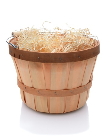 basket: Bushel basket with a wood handle and stuffed with straw over a white background and slight reflection.