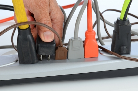 Closeup of a mans hand inserting a plug into a crowded power strip.