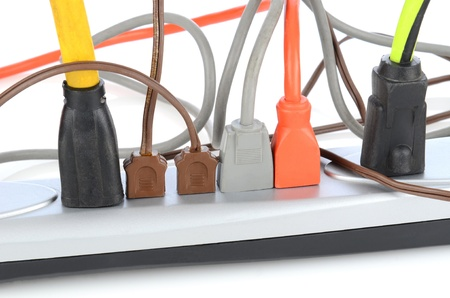 messy: Closeup of an electrical power strip with several different cords plugged in.