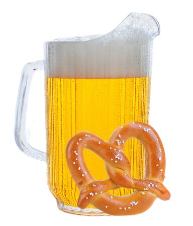 bar counters: Pitcher of beer in vertical format over white, with a large soft pretzel leaning against. Stock Photo