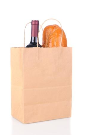bolsa de pan: Un papel marrón bolsa de supermercado con asas y una botella de vino y pan de pan francés. Formato vertical sobre un fondo blanco con la reflexión ligera. Foto de archivo
