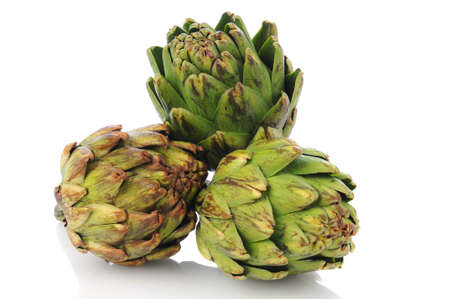 A group of three artichokes on a white background with reflection. Closeup in horizontal format. Stock Photo - 13996424