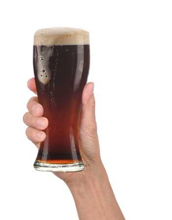 Closeup of a male hand holding up a glass of foamy dark ale over a white background. Vertical format with drip running down the side of the beer glass. photo
