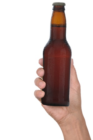 Man's hand holding up a brown beer bottle without label over a white background vertical format Foto de archivo