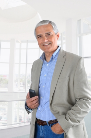 casually: A middle aged businessman in office setting hodling cell phone. Man is casually dressed. Vertical format.